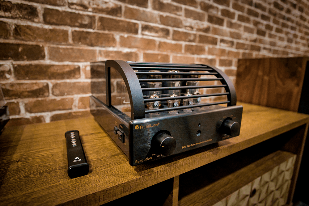evolution tube amp on a table next to a remote.